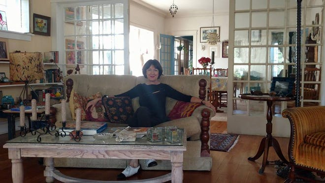 Mary D. Wells sits in the living area of the Craftsman home she grew up in. The home is part of the Sunset Heights Tour of Homes on Saturday.