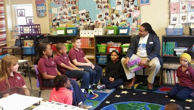 Volunteer Dwayne Wright reads to students at the York City School District during the 2015 Reading IS Essential: 100 Men Reading Program event.