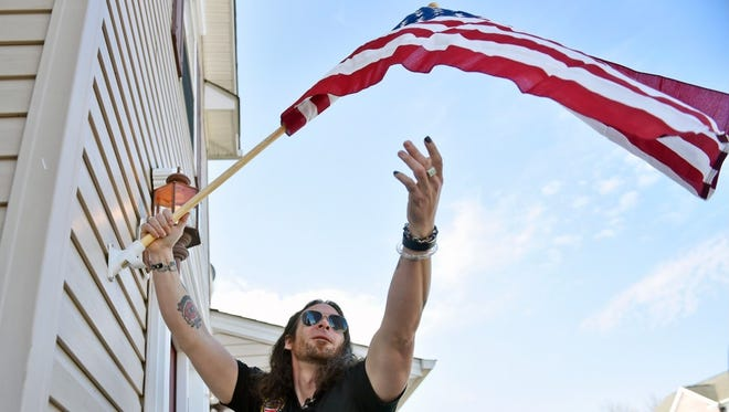 Ian Stauffer displays the American flag outside his new house Thursday, Feb. 23, 2017, in Conewago Township.