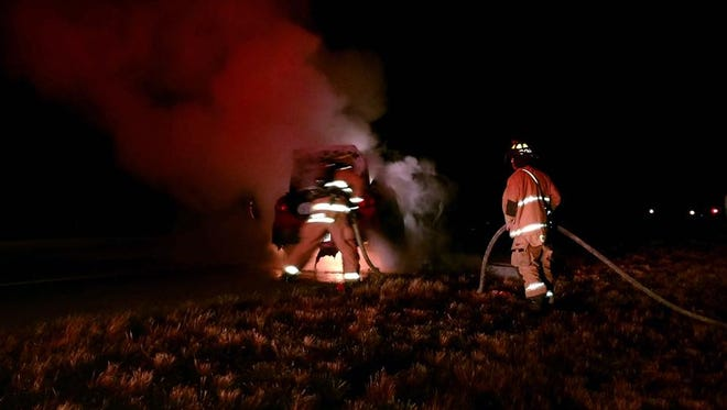 St. Lucie County Fire District firefighters extinguish a car fire on Interstate 95 early Saturday, March 25, 2017, in Port St. Lucie.