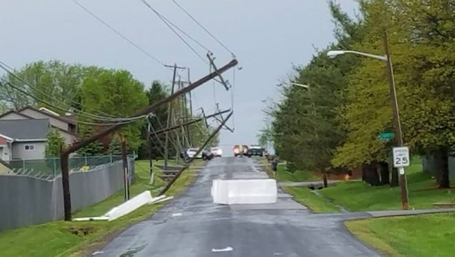 Utility poles are left hanging on North Adams Street, near Fleet Farm, after a storm went through Marshfield Wednesday afternoon.