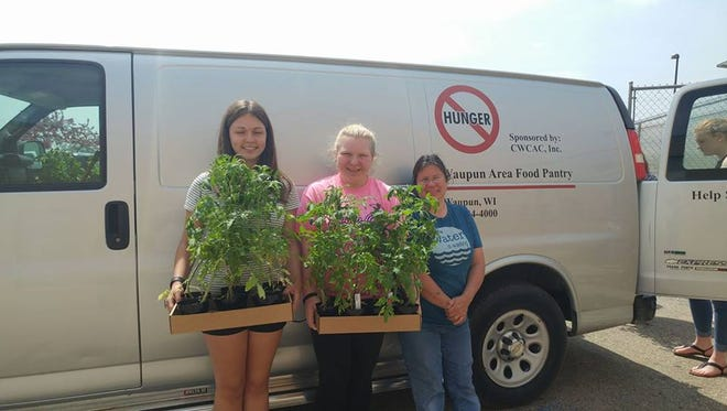 Waupun FFA members Brianna Asmus and Roni Schulz present some of the more than 400 tomato plants that the Waupun Agriculture Education students raised and donated to the Waupun Food Pantry and Community Garden coordinator, Terri Respaljie, right.