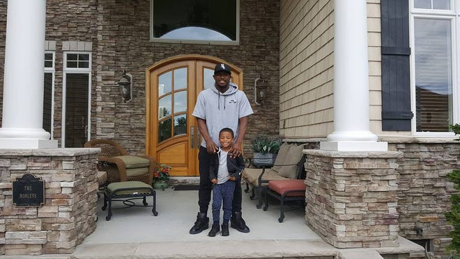 NFL running back LeSean McCoy stands outside of his rented house in Rehoboth Beach with his son on June 23.