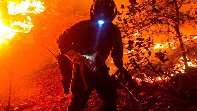 A member of the Flagstaff Hotshots carries a fawn away from the fire on Friday, June 30.