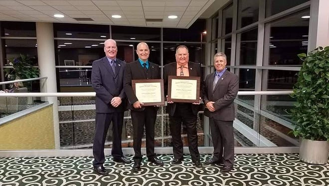Sheriff Tim Donnellon and Undersherfiff Tom Buckley congratulate corrections sergeants Scott Philben, left, and Mike Witkowski, who  have graduated from the Eastern Michigan University Staff and Command Executive Leadership program.
