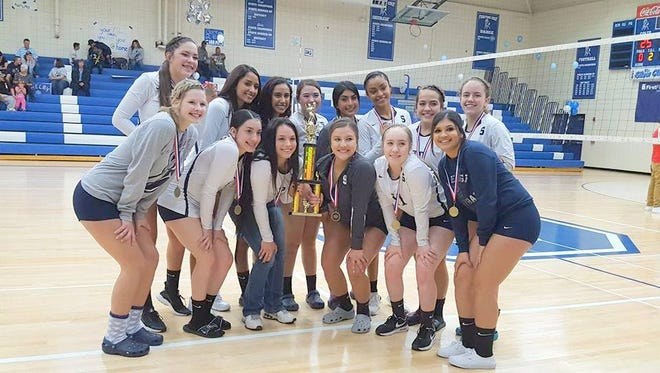 The Silver High volleyball team poses with its District 3-4A Tournament trophy after beating Cobre, 3-0, Saturday afternoon at home.