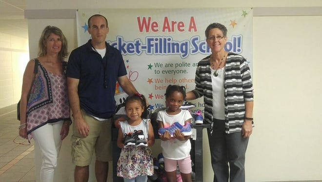 Gigi Suntum, left, director of Caring Children Clothing Children, stands with Kyle Harvey, physical education coach, and Ivy Menken, principal at Warfield Elementary and two students holding sneakers given by 4Cs to the school's lending closet.