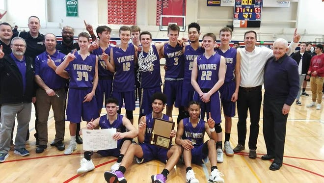 North Kitsap's boys basketball team poses with the West Central District trophy after beating Fife on Saturday.