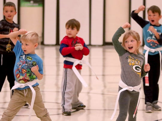 Students practice a defensive high block during the fourth after-school Anti-Bullying Martial Arts session at Muskego Elementary School on Oct. 11. Students learn a bully is someone you know who does not show respect to others.