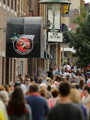 Music fans stream along College Avenue in downtown