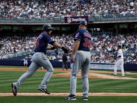 Indians third base coach Joel Skinner congratulates Grady Sizemore after a 2009 home run.