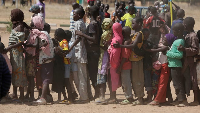 In this November 2014 photo, children displaced after attacks by Boko Haram, line up in the camp of internal displace people, in Yola, Nigeria. Seven children had been reunited with parents lost in the chaos of attacks in Nigeria's northeastern Islamic insurgency but hundreds more remain alone, officials say.