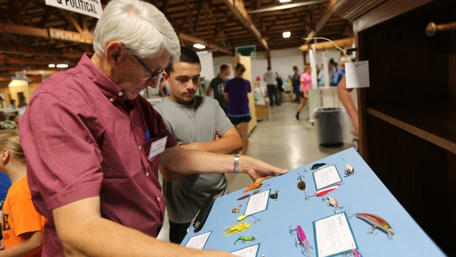 Judge Jim Barthel looks over a fishing display project by Zachary Blashka, 13, of the Rockland Sunshine 4-H Club at the 2016 Manitowoc County Fair. The wooden cabinet was also made by Blashka, and both were give first place ribbons.