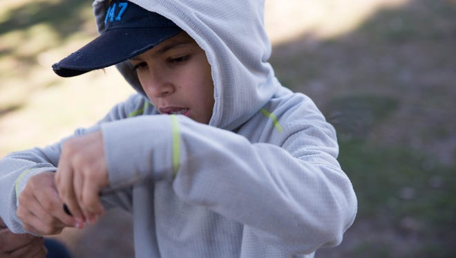 Jayden Amador, 10, runs fishing line through his pole before he starts fishing at the duck pond at New Mexico State University,Saturday, March 25, 2017, during the Kids Fishing Clinic put on by the New Mexico Department of Game and Fish and the Mesilla Valley Flyfishers.
