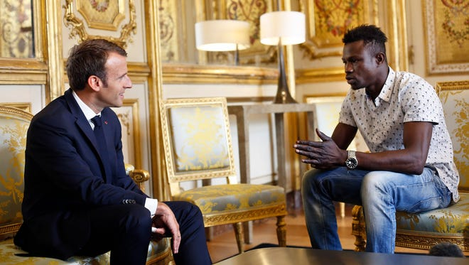 French President Emmanuel Macron, left, meets with Mamoudou Gassama, 22, from Mali, at the presidential Elysee Palace in Paris on Monday.
