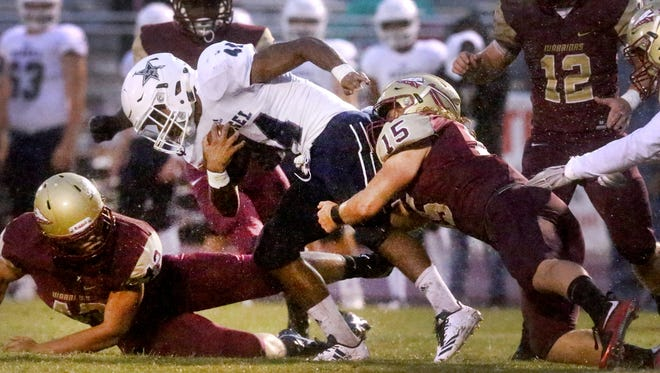 Siegel's Lelan Wihoite (44) runs the ball as Riverdale's Brady Stokes (15) takles him during the game, on Friday, Sept. 1, 2017, at Riverdale.