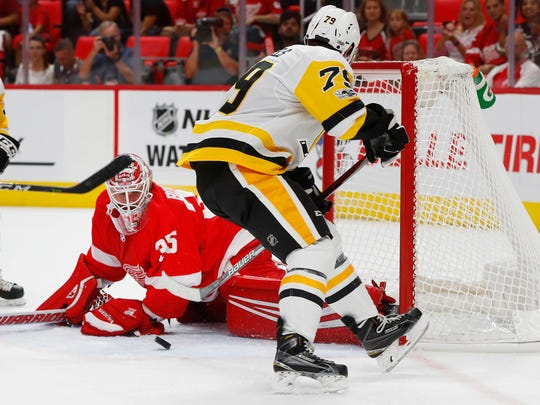 Red Wings goalie Jimmy Howard stops a shot by Penguins left wing Frederik Tiffels during the first period Sept. 25, 2017 in Detroit.