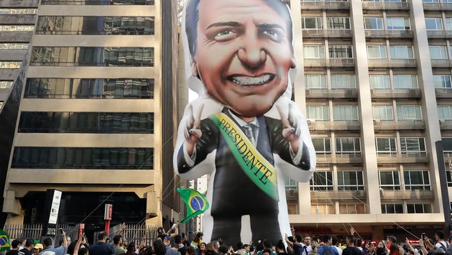 "FILE - In this Sept. 9, 2018 file photo, supporters of Jair Bolsonaro, presidential candidate for the National Social Liberal Party who was stabbed during a campaign event days ago, exhibit a large, inflatable doll in his image to show support for him, in Sao Paulo, Brazil. Silas Malafaia, one of Brazil's most influential pastors, visited Bolsonaro in the hospital. ""God is an expert in turning chaos into a blessing,"" Malafaia said in a video he posted on YouTube from Bolsonaro's hospital room. (AP Photo/Andre Penner, File)"
