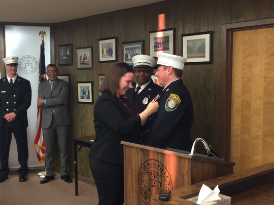 New Millville Fire Department  Lt. John Garton stands still while his wife Kristi pins on his badge. New Lt. Kevin Hall observes.