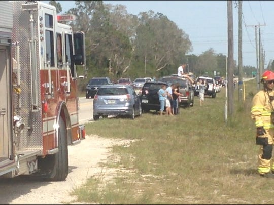 Spectators lined Alico Road on Sunday afternoon to watch firefighters attack a grass and brush fire.