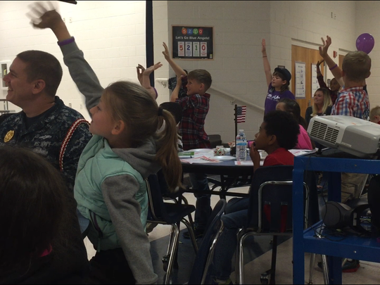 Students raise their hands to answer a question at Thursday's Blue Angels Elementary Little Hero's Military Breakfast.