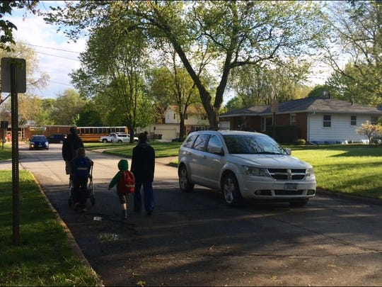 A car drives around Mike Draper and his family as they