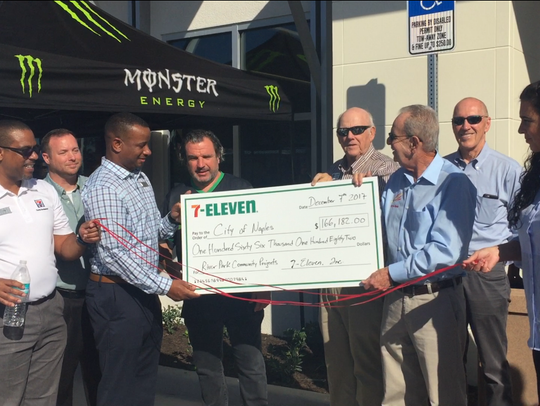 7-Eleven officials present Naples Mayor Bill Barnett a check for $166,000 to fund improvements in the low-income River Park neighborhood. The company offered the payment after the Naples Daily News reported on 7-Eleven's unfulfilled requirements from the City Council's development order.