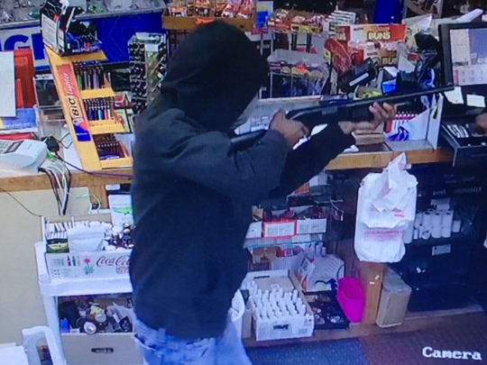 A masked black man armed with a shotgun is pictured