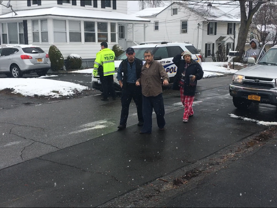 Responders aiding a man who was inside a home and sickened