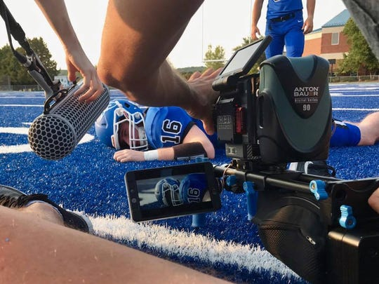 Chris Norton lies face down on the turf at Luther College's football stadium in a reenactment of the moment he broke his neck in 2010. The non-profit inspirational documentary company Fotolanthropy is making a film about Norton's life since the injury.