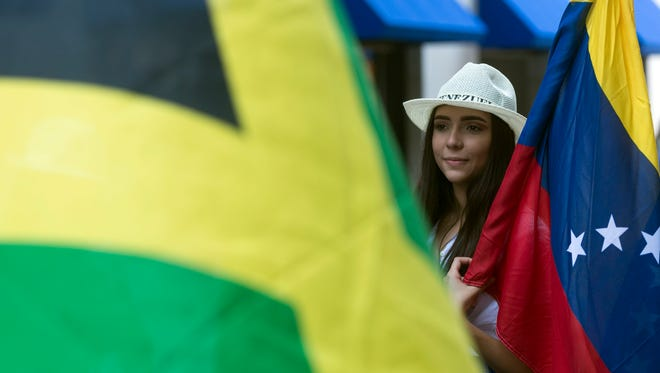 Valeria Mosquera carries the flag of Venezuela while another participant carries the flag of Jamaica during HoLa Festival's Parade of Nations at Market Square on Sept. 17, 2017. This year's festival will be held Sept. 29-30.