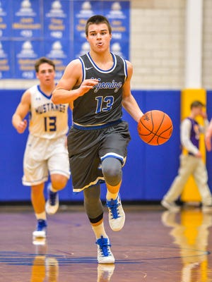 Wyoming sophmore Joey Edmonds dribbles the ball up court against Madeira. Michael Noyes for the Enquirer