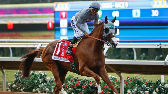 California Chrome jockey Victor Espinoza smiles as the horse crosses the finish line with a victory in the Pacific Classic at Del Mar Thoroughbred Club on Saturday, Aug. 20, 2016, in Del Mar, Calif. (AP Photo/Lenny Ignelzi)