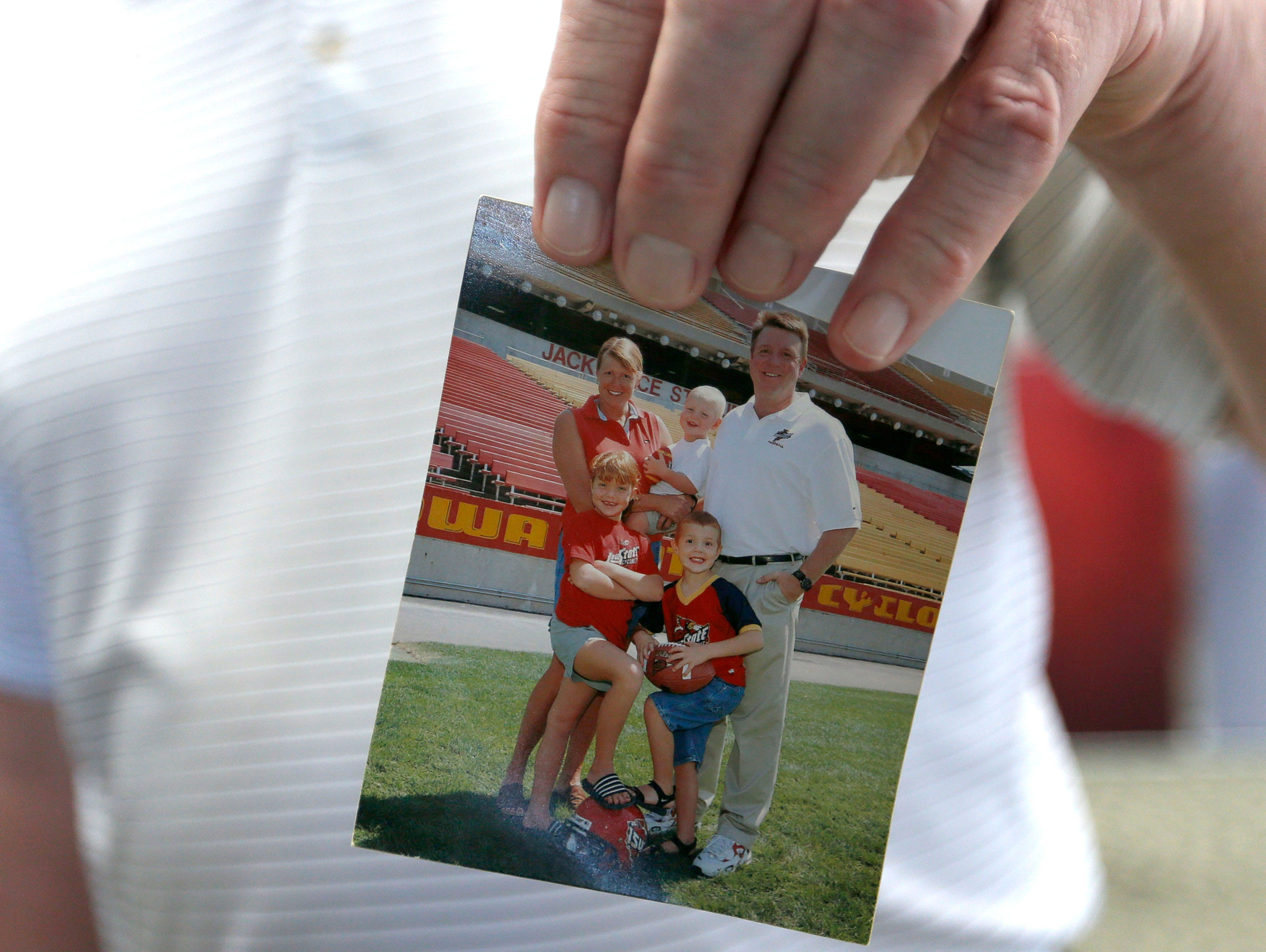 Terry Allen holds a family photo taken on the University of Iowa football field after his son (pictured center) announced his decision to play football at Iowa State during a press conference on Friday, Jan. 29, 2016.