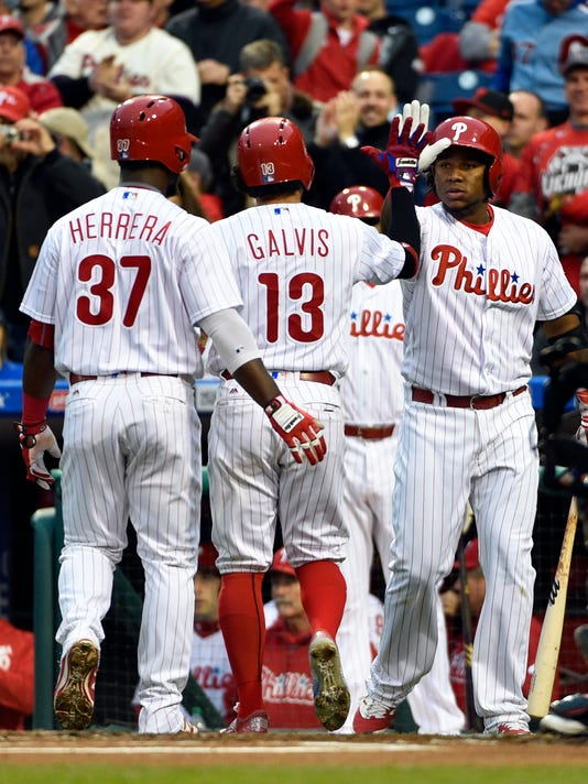 Philadelphia Phillies' Freddy Galvis, center, is greeted at home by Maikel Franco, left, and Odubel Herrera after hitting a two run home run off Cleveland Indians starting pitcher Trevor Bauer during the first inning of a baseball game, Saturday, April 30, 2016, in Philadelphia. (AP Photo/Derik Hamilton)