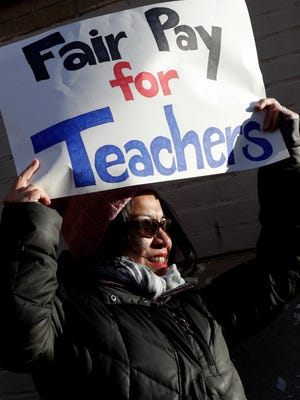 Maria Corpuz, who's son, Blake Zimmer is a sixth grade student at The Academy I Middle School, joins educators during a strike outside of the school, Friday, March 16, 2018, in Jersey City, N.J. The strike began early Friday after the teachers union and the district failed to reach a deal. The two sides have been negotiating since last year, but talks have stalled over health care costs. (AP Photo/Julio Cortez)