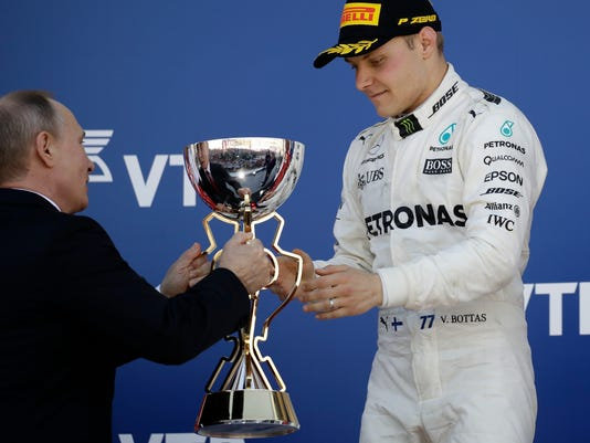 Mercedes driver Valtteri Bottas of Finland receives the trophy from Russia's president Vladimir Putin for his victory at the Formula One Russian Grand Prix at the 'Sochi Autodrom' circuit, in Sochi, Russia, Sunday, April. 30, 2017. (AP Photo/Pavel Golovkin)