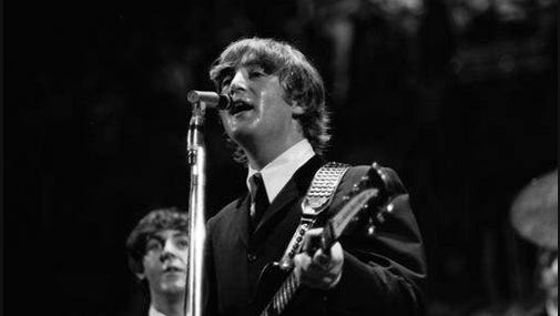 In this 1964 photo taken by Walt Burton and provided by Christopher Hoeting, John Lennon, front, and Paul McCartney of the Beatles, perform during a concert in Cincinnati in 1964.