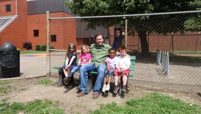 Brett Mulzer sits with EVSC elementary school students on one of the 23 buddy benches he donated to local schools.