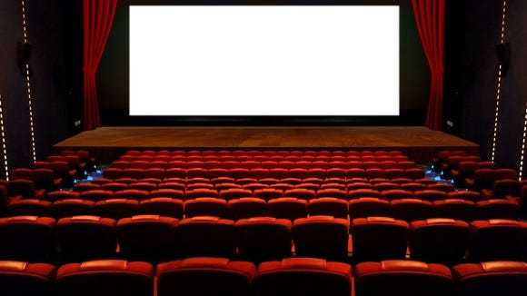Empty movie theater with a white screen.
