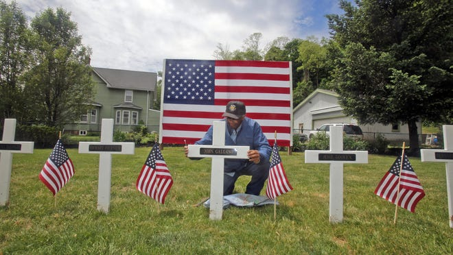 Richard Deloatch, a member of the Veterans of Foreign Wars post in Piermont, installs memorials Thursday honoring local residents killed in World War II at the war memorial site on Piermont Avenue in Piermont. As they do each year, the memorial crosses will stay up through the Memorial Day weekend.