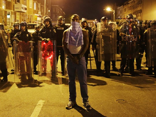 A man stands in front of a line of police officers