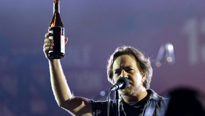 Eddie Vedder from Pearl Jam toast with the public while he performs  during the fourth annual Global Citizen Festival.