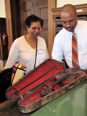 Shirley Burke of West Bloomfield, Mich., collection donor, with Rex Ellis, associate director for curatorial affairs, National Museum of African American History and Culture in Washington, D.C. She donated a violin that had been in her family for generations; her ancestor Jesse Burke played it during his time as a slave.