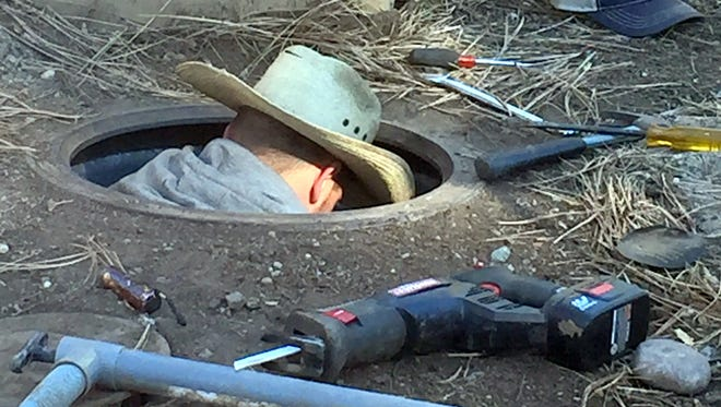 An employee of C.J. Mead is nearly fully submerged in a deep hole trying to extract an old water meter in Ruidoso.