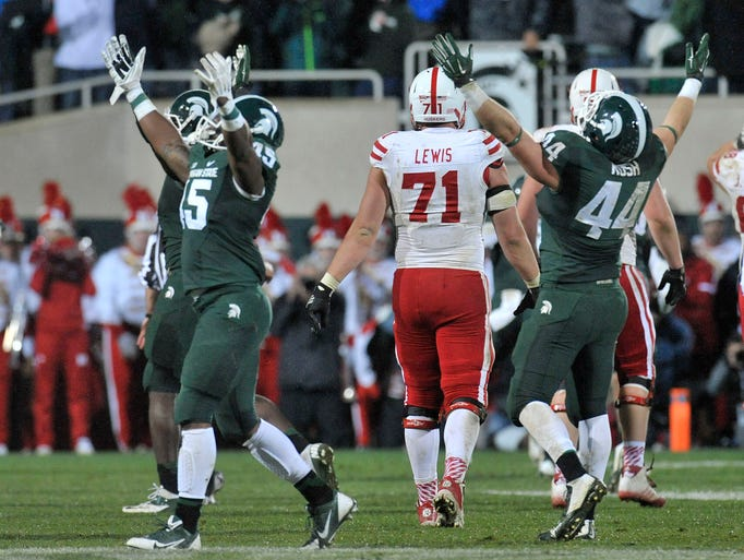 Darien Harris, left, and Marcus Rush right of Michigan State celebrate after pressuring Nebraska quarterback Tommy Armstrong Jr. into throwing an interception in the final seconds of the game on Saturday, Oct. 5,  2014 at Spartan Stadium in East Lansing, Mich. The Spartans won, 27-22.
