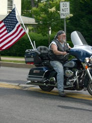 A motorcyclist displays a flag at Mercersburg's Memorial