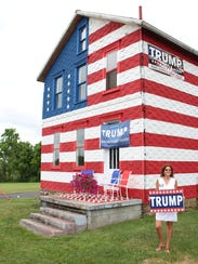 Leslie Rossi poses by a large Donald Trump signs in