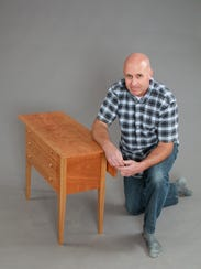 Kevin Deraps kneels by a table he made at Vermont Woodworking