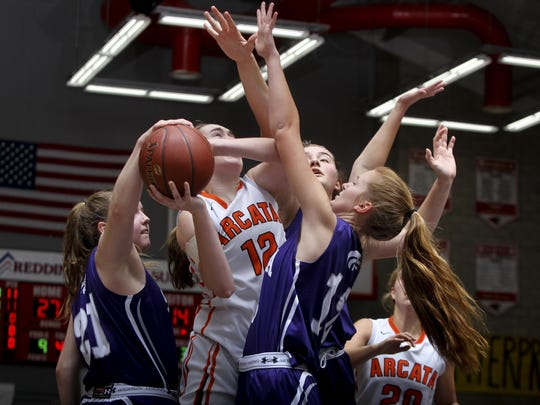 Arcata's Kaylie McCracken goes up for a basket against Shasta's Cate Walton, from left, Sophie Wood, and Madison Pulice in Saturdays championship game in the Harlan Carter girls tournament. Arcata won 54-44.